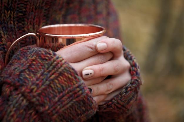 Mani femminili del primo piano in un maglione caldo che tiene una tazza di rame con tè, concetto accogliente di autunno Foto Premium