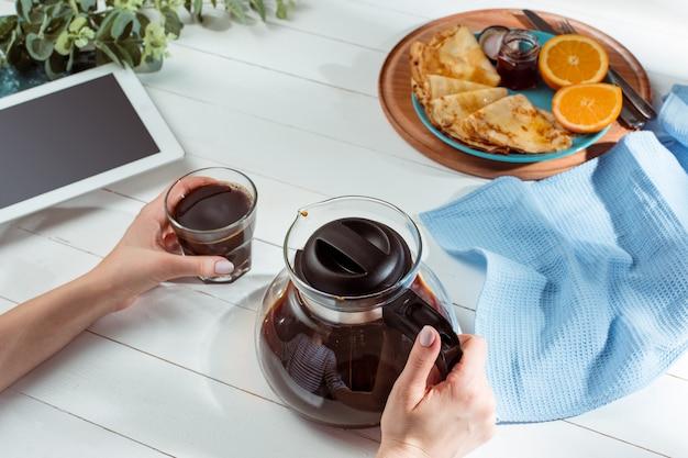 Mani femminili e frittelle con succo. colazione salutare Foto Gratuite