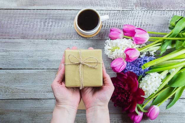 Mani femminili in possesso di un regalo o scatola regalo, tulipani fiori, peonia, giacinto e tazza di caffè nero Foto Premium