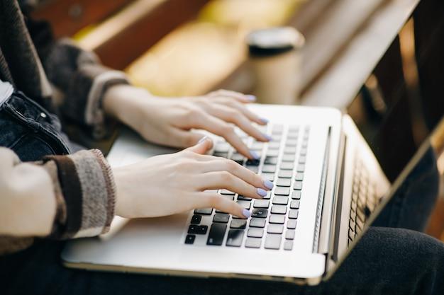 Mani femminili su un computer portatile nel parco Foto Premium
