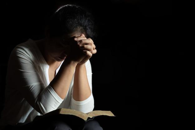 Mani giunte in preghiera su una sacra bibbia in chiesa Foto Gratuite