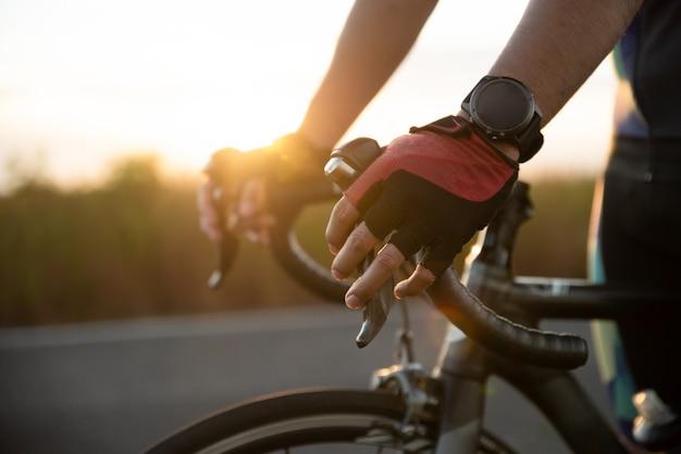 Mani in guanti che tengono il manubrio della bicicletta stradale Foto Premium