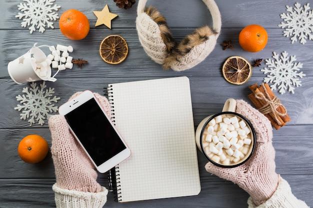 Mani in guanti con smartphone e tazza con marshmallow vicino a notebook e fiocchi di neve di carta Foto Gratuite