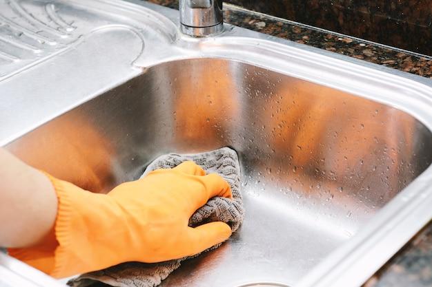 Mani in guanti di gomma lavare i piatti con spon Foto Premium