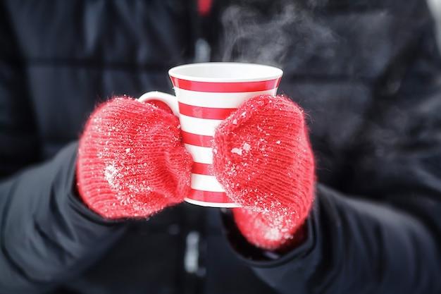 Mani in guanti rossi che tengono la tazza calda di inverno con vapore Foto Premium
