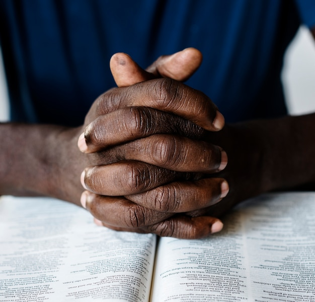 Mani maschii afroamericane che riposano su una bibbia aperta Foto Gratuite
