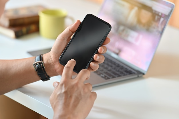 Mani maschii che tengono telefono cellulare in ufficio. Foto Premium