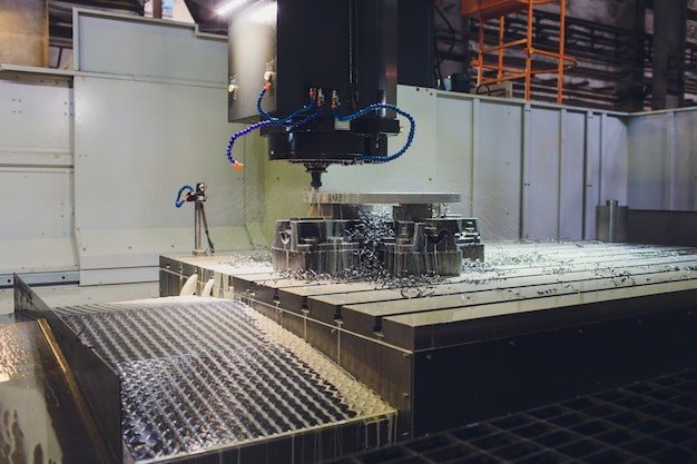 Mani maschii del lavoratore che funzionano con la macchina di cnc alla fabbrica con i torni. Foto Premium