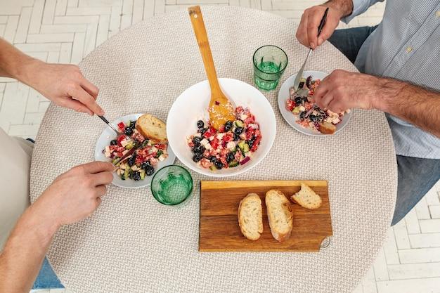 Mani maschii di vista superiore che servono insalata deliziosa Foto Gratuite