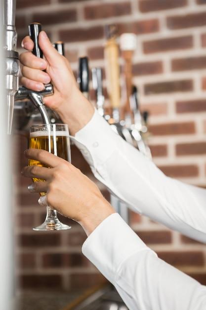 Mani maschili che versano birra Foto Premium