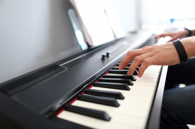 Mani maschili del musicista che giocano piano elettrico moderno Foto Premium
