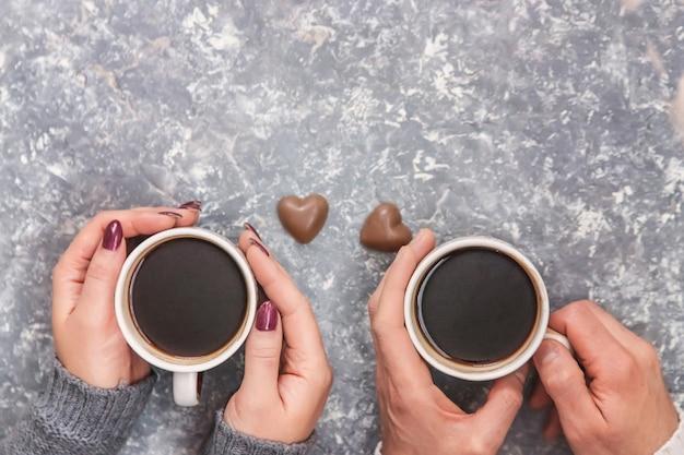 Mani maschili e femminile che tengono tazze di caffè. messa a fuoco selettiva Foto Premium