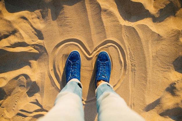 Mani maschili in blue jeans e scarpe da ginnastica eleganti in piedi all'interno dipinto cuore sulla sabbia. Foto Premium