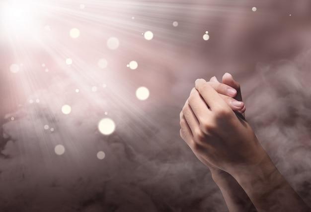 Mani maschili in posizione di preghiera con raggio Foto Premium
