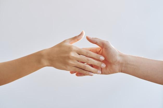 Mani nude di due persone irriconoscibili che si allungano l'una verso l'altra Foto Gratuite