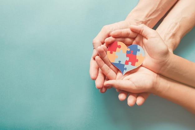 Mani per adulti e bambini che tengono a forma di cuore puzzle, consapevolezza dell'autismo, concetto di sostegno della famiglia dello spettro autistico, giornata mondiale della consapevolezza dell'autismo Foto Premium
