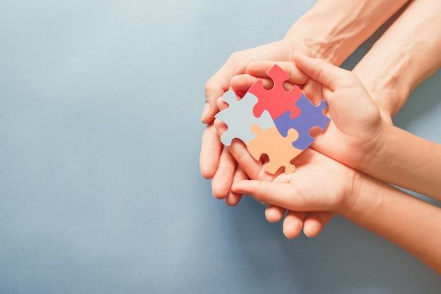 Mani per adulti e bambini che tengono forma di puzzle, consapevolezza dell'autismo, concetto di sostegno della famiglia dello spettro autistico, giornata mondiale della consapevolezza dell'autismo Foto Premium