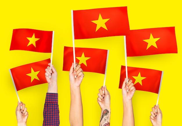 Mani sventolando bandiere del vietnam Foto Gratuite