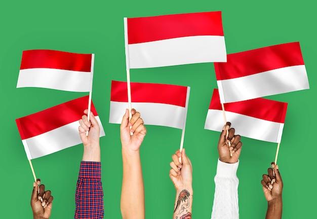 Mani sventolando bandiere dell'indonesia Foto Gratuite