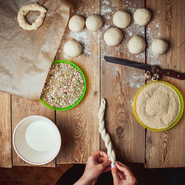Mani torcendo la pasta per preparare il bagel turco simit vista dall'alto. Foto Gratuite