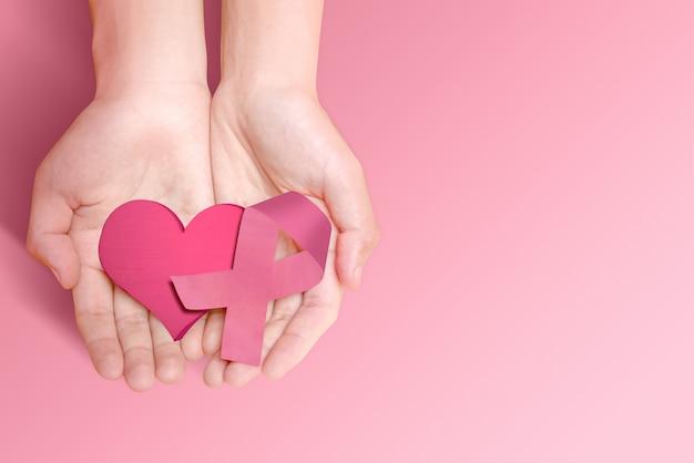 Mani umane che mostrano un cuore rosa e un nastro rosa Foto Premium
