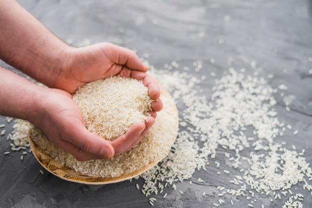 Mani umane che selezionano il riso dal piatto di legno sopra fondo concreto Foto Gratuite
