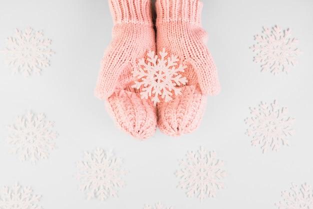 Mani umane in muffole con fiocco di neve di carta Foto Gratuite