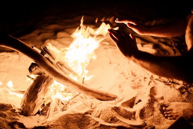 Mani vicino al fuoco sulla spiaggia Foto Gratuite