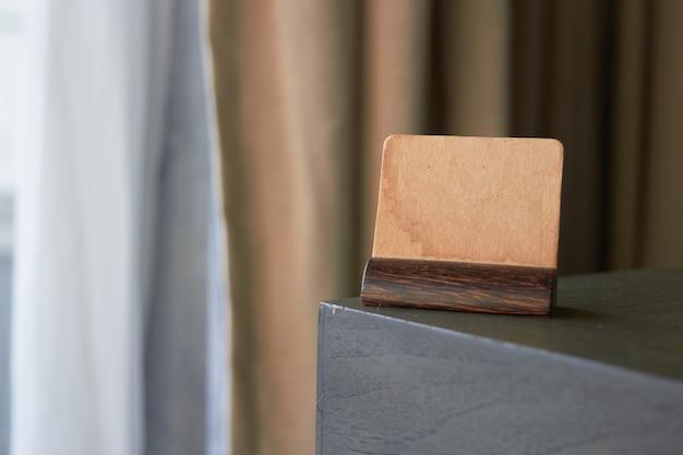 Manichino di carta vintage marrone segno o simbolo titolare della carta etichetta sull'angolo del tavolo Foto Premium