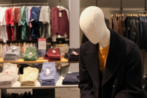 Manichino in autunno o cappotto invernale presso il negozio di abbigliamento maschile. tempo di stagione delle vendite e degli sconti. Foto Premium