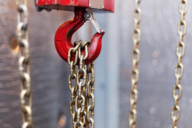 Manico a catena metallico con gancio rosso in locale tecnico. gancio cargo per gru. Foto Premium