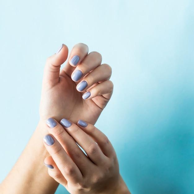 Manicure blu sulle unghie femminili su sfondo blu Foto Premium