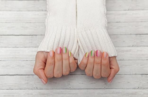 Manicure moderna multicolore, design delle unghie, umore estivo, mani in una vista dall'alto maglione bianco Foto Premium