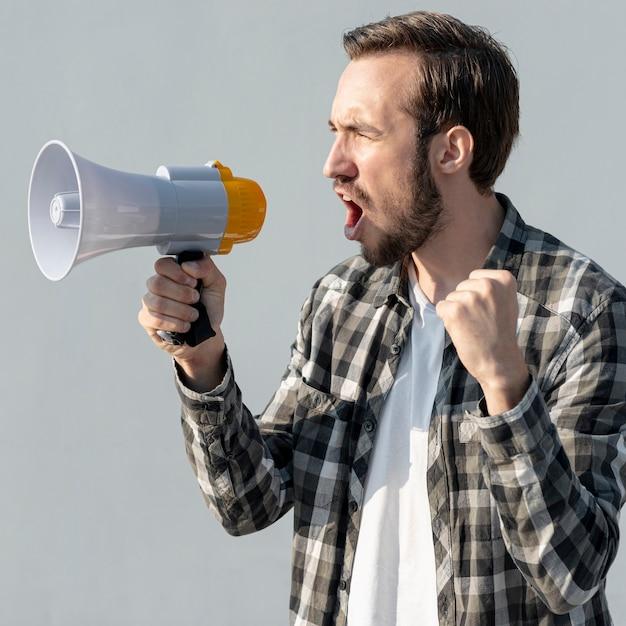 Manifestante con il megafono che grida Foto Gratuite