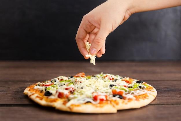 Mano aggiungendo topping di formaggio alla pizza Foto Gratuite