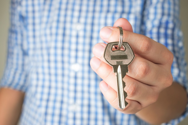 Mano asiatica che tiene la chiave di casa Foto Premium