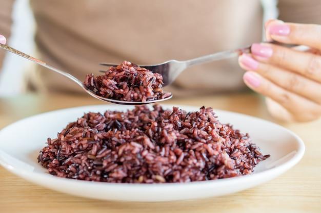 Mano asiatica della donna che mangia la bacca sana del riso Foto Premium