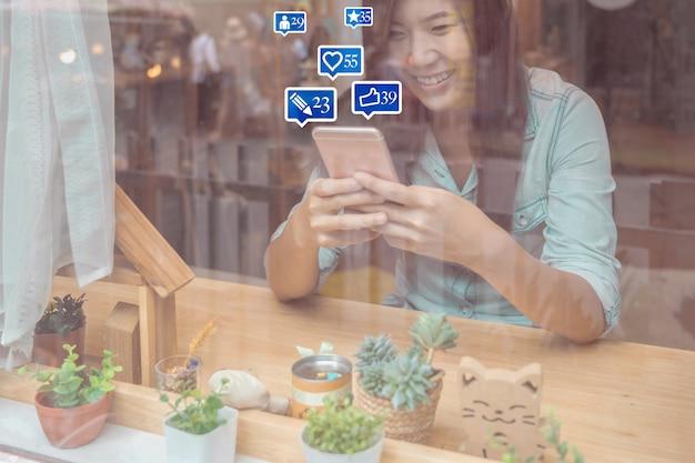 Mano asiatica della donna di affari facendo uso del telefono cellulare astuto per i media sociali del netwrok con il numero di simili Foto Premium