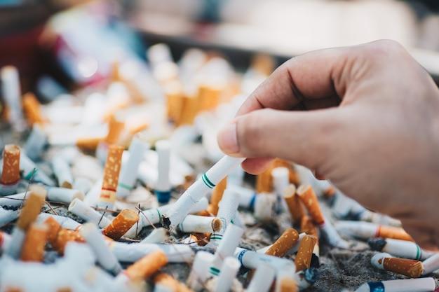 Mano che mette la sigaretta su un posacenere con mozziconi di sigaretta conficcati nella cenere Foto Premium