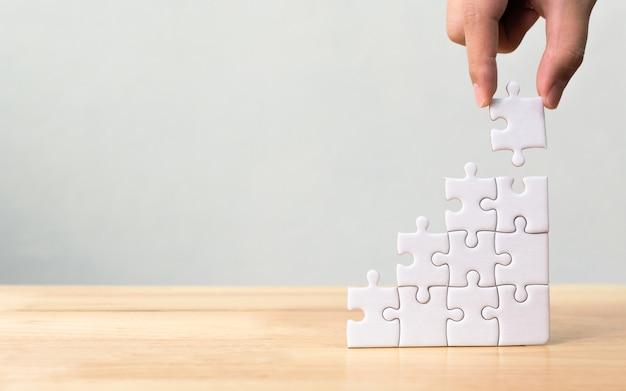 Mano che organizza jigsaw puzzle accatastamento come scala sul tavolo di legno Foto Premium