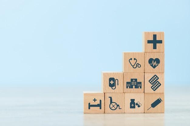 Mano che organizza l'impilamento del blocco di legno con l'icona di assistenza sanitaria medica. Foto Premium