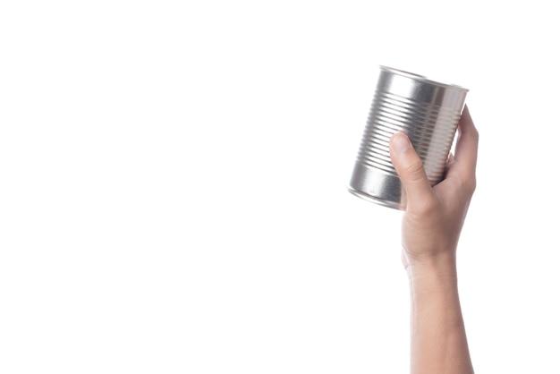 Mano che regge barattolo di latta o acciaio in alluminio per alimenti Foto Premium