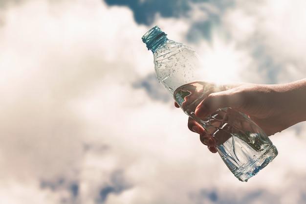 Mano che regge una bottiglia di plastica trasparente di pura acqua potabile Foto Premium