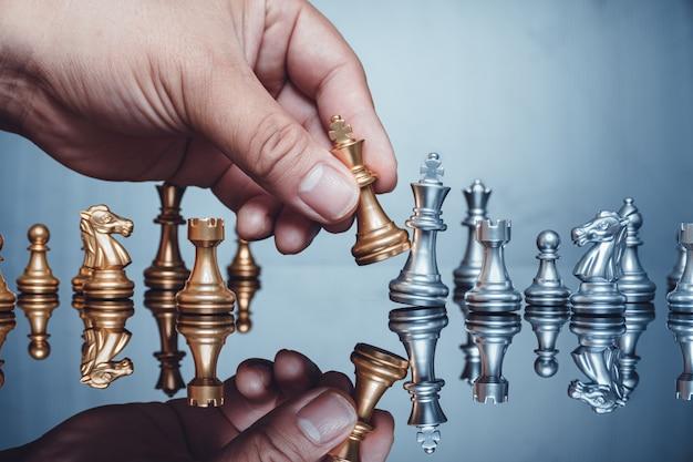 Mano che si muove la figura di scacchi dorata del pezzo di re nel gioco di successo della concorrenza strategia aziendale Foto Premium