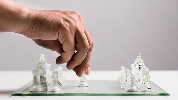 Mano che si muove pezzi di scacchi trasparenti Foto Gratuite