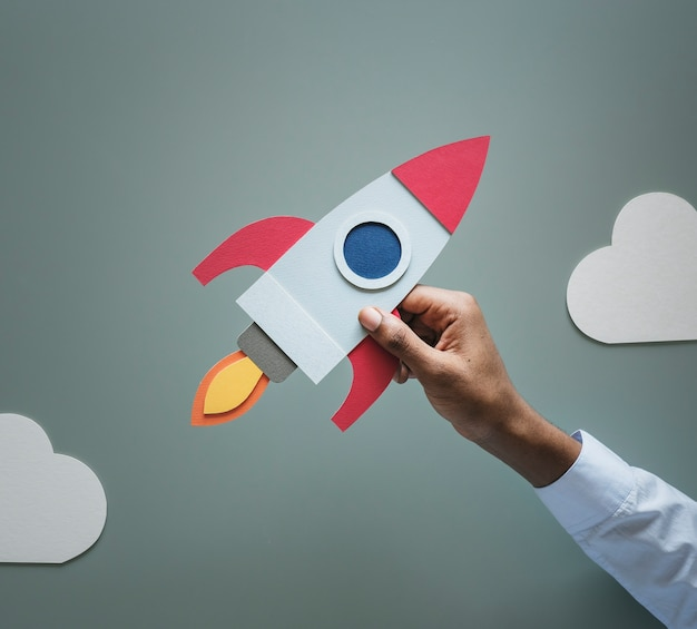 Mano che tiene business startup rocketship Foto Premium