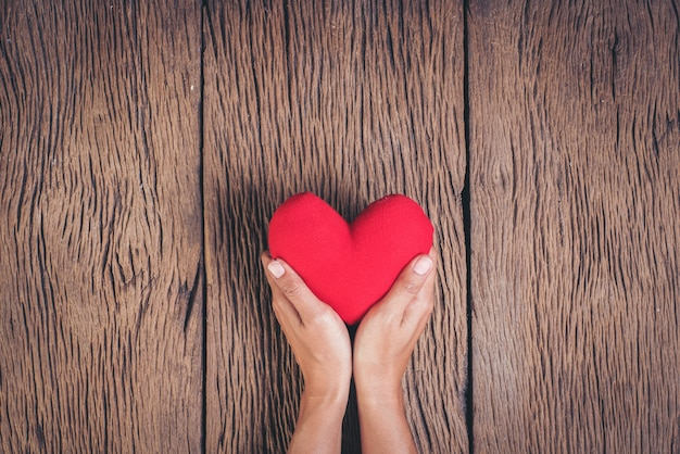 Mano che tiene cuore rosso su sfondo di legno Foto Gratuite