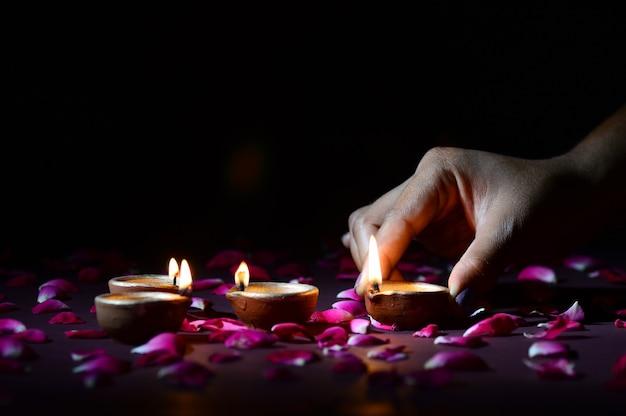 Mano che tiene e organizzare la lanterna (diya) durante il festival delle luci diwali Foto Premium