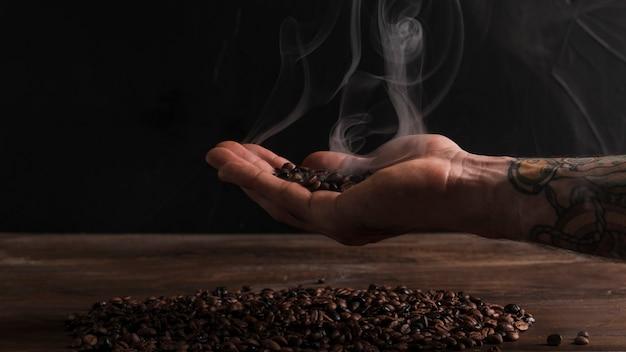Mano che tiene i chicchi di caffè caldi Foto Gratuite