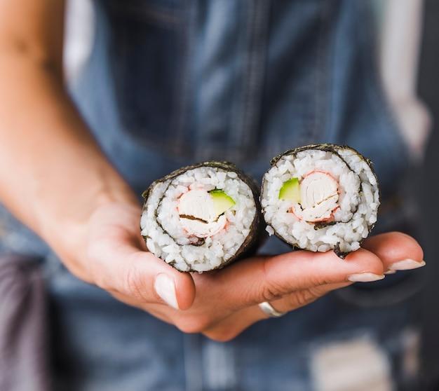 Mano che tiene i rotoli di sushi Foto Gratuite